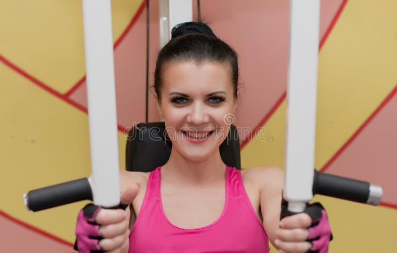 Piękna dziewczyna ćwiczy w sprawność fizyczna klubie na symulancie obraz stock