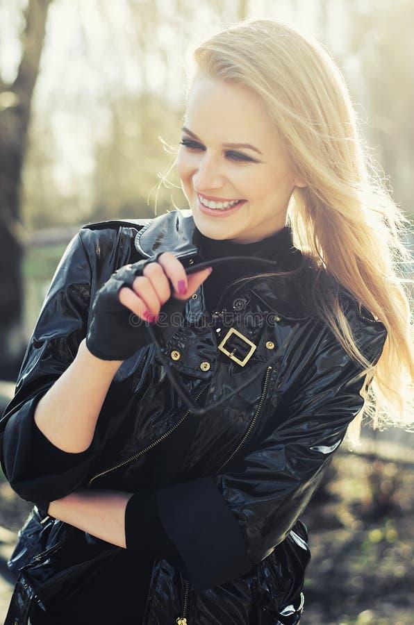 Piękna dziewczyna śmia się w parku w czarnej kurtce fotografia royalty free