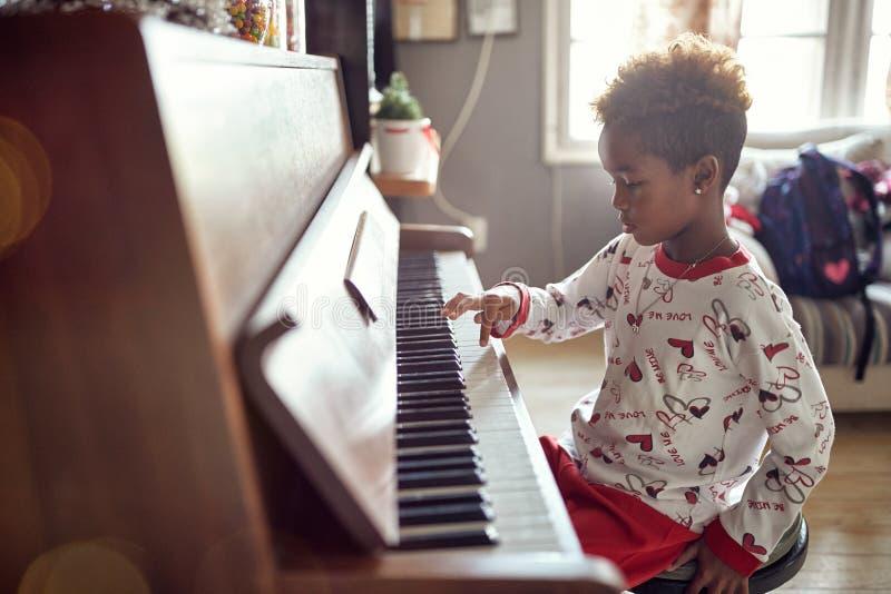 Piękna dziewczyna bawić się na fortepianowej mas muzyce Pojęć boże narodzenia, nowy rok, wakacje, rodzinny szczęście, dzieciństwo obraz stock