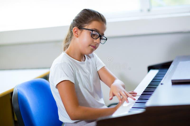 Piękna dziewczyna bawić się pianino przy muzyczną szkołą zdjęcia stock