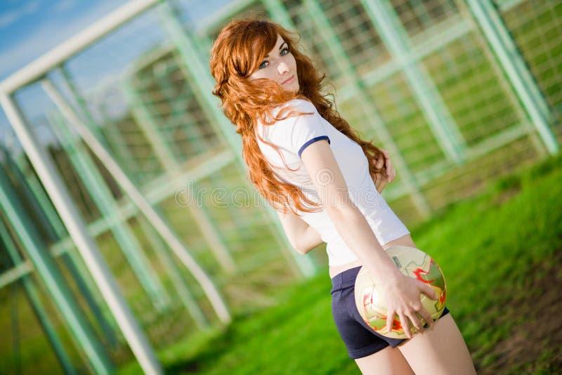piękna dziewczyna bawić się rudzielec piłkę nożną obraz stock