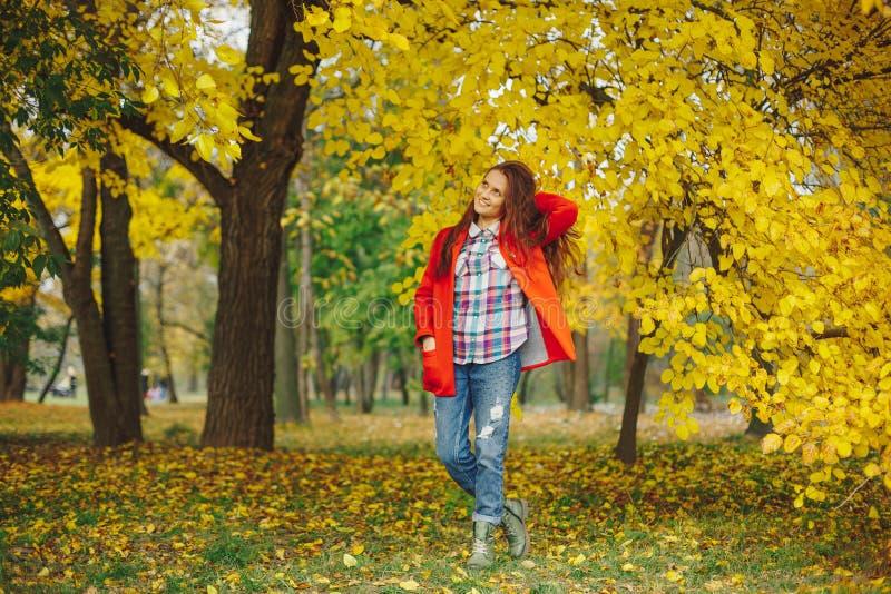 Piękna dziewczyna bawić się z włosy podczas gdy chodzący w jesieni normie zdjęcie stock