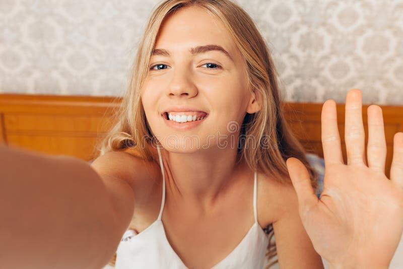 Piękna dziewczyna bierze selfie budzi się up w jej łóżku w mornin fotografia stock
