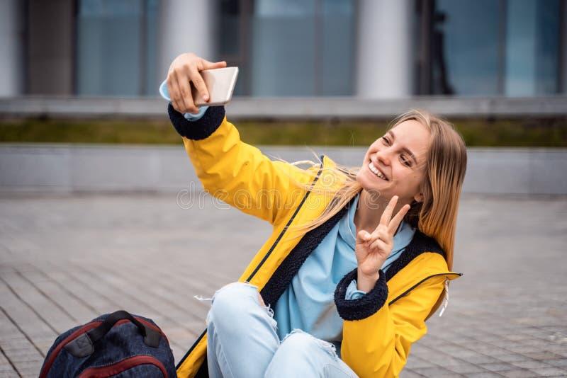 Piękna dziewczyna bierze selfie na smartphone i siedzi na deskorolka fotografia royalty free