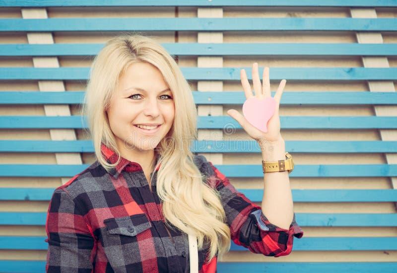 Piękna dziewczyna blisko ściany na ulicie w lecie Na nastroszonym ręki czerwieni papieru sercu Kolorowa modniś fotografia obraz royalty free