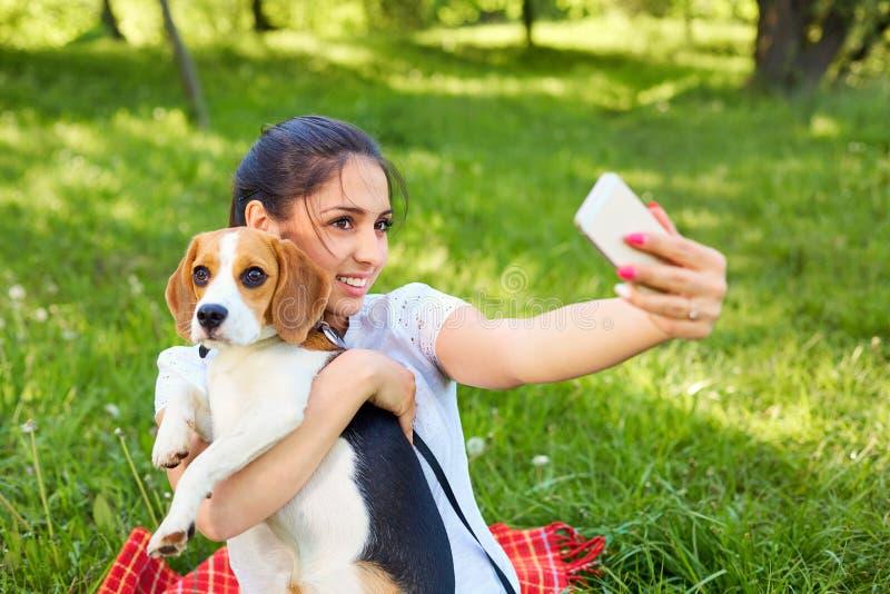 Piękna dziewczyna brać obrazki jej jaźń z psem Instagram zdjęcie stock