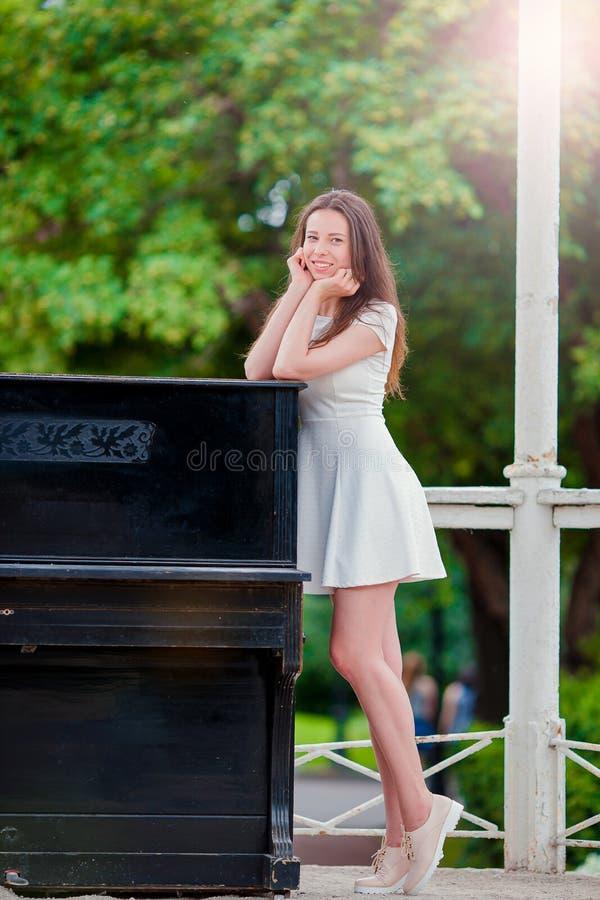 Piękna dziewczyna cieszy się lato weekend w parkowym plenerowym pobliskim dużym pianinie Młoda kobieta na wakacji outdoors ono uś fotografia royalty free