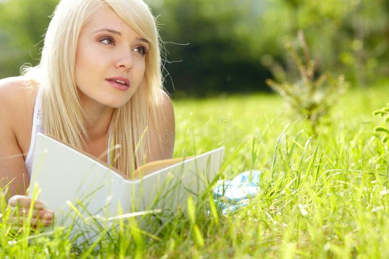 Piękna dziewczyna czyta książkę plenerową obrazy royalty free