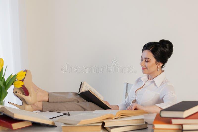 Piękna dziewczyna czyta książki przy stołowym narządzaniem dla egzaminu obraz royalty free