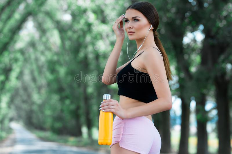Piękna dziewczyna dostaje przygotowywający dla jogging w parku Z termos butelką w ręce obrazy stock