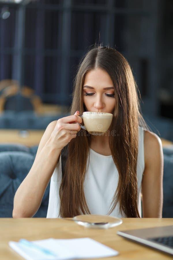 Piękna dziewczyna i filiżanka cappuccino zdjęcia stock