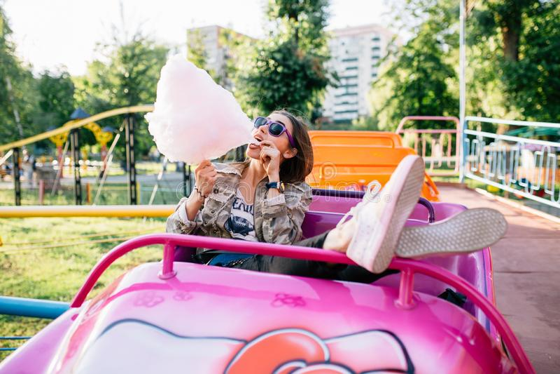 Piękna dziewczyna je bawełnianego cukierek, cieszy się słonecznego dzień przy parkiem rozrywkim fotografia royalty free