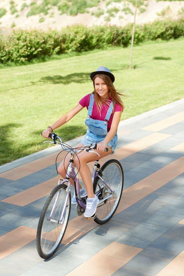 Piękna dziewczyna jedzie bicykl w miasto parku fotografia stock