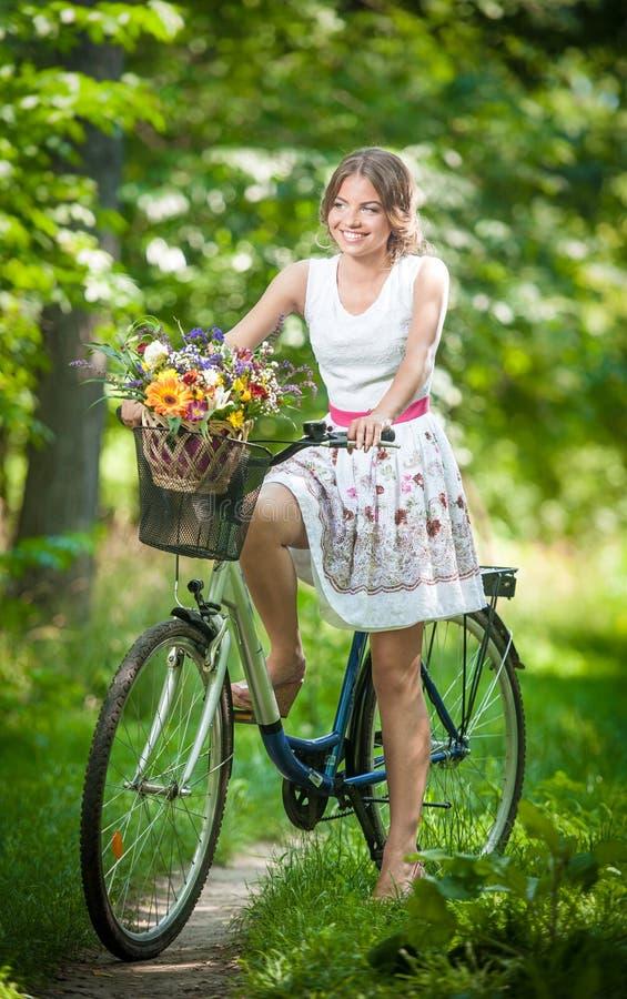 Piękna dziewczyna jest ubranym ładną biel suknię ma zabawę w parku z bicyklem Zdrowy plenerowy stylu życia pojęcie Rocznik scener zdjęcia stock