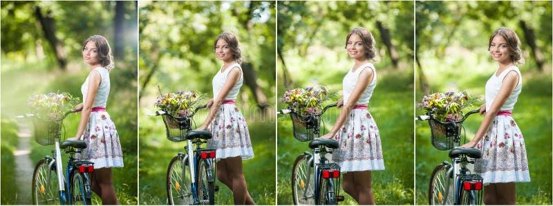 Piękna dziewczyna jest ubranym ładną biel suknię ma zabawę w parku z bicyklem Zdrowy plenerowy stylu życia pojęcie Rocznik scener obrazy stock