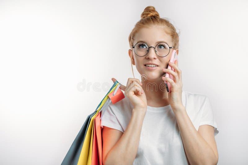 Piękna dziewczyna jest ubranym jej czerwonego włosy w babeczce trzyma torba na zakupy zdjęcia stock