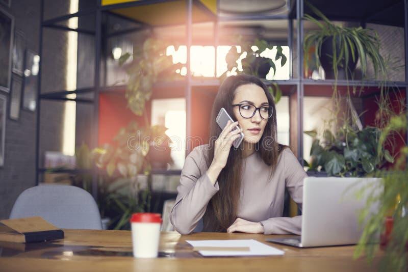 Piękna dziewczyna jest ubranym oczu szkła w coworking studiu opowiada smartphone Pojęcie młodzi ludzie pracuje z mobilnymi gadżet fotografia stock