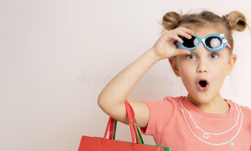 Piękna dziewczyna jest ubranym suknię i okulary przeciwsłonecznych trzyma torby na zakupy zdjęcie royalty free