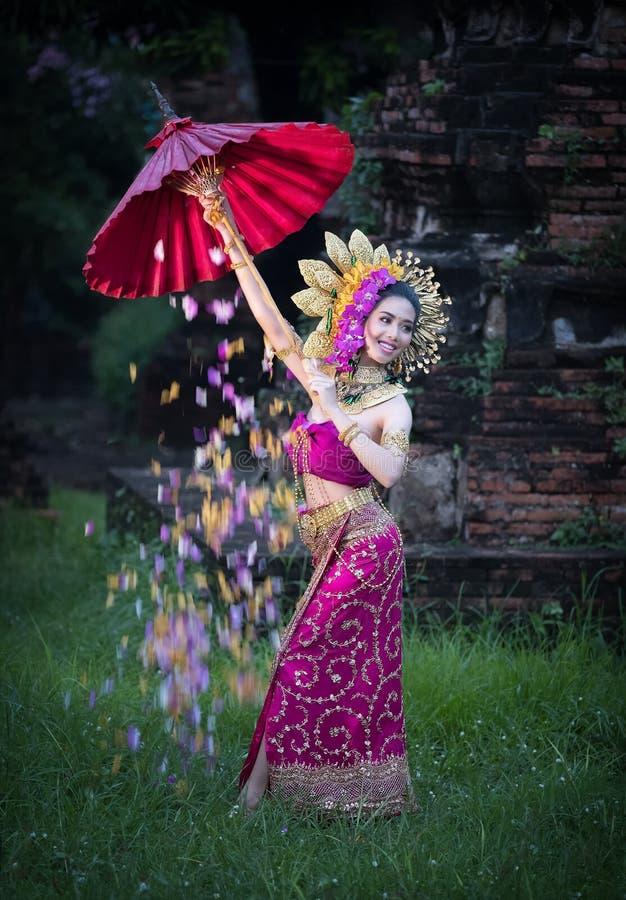 Piękna dziewczyna jest ubranym Tajlandzką suknię i parasolowy kwiat płyniemy backg obraz stock