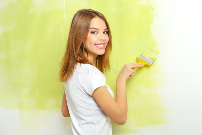 Piękna dziewczyna maluje ścianę obraz royalty free