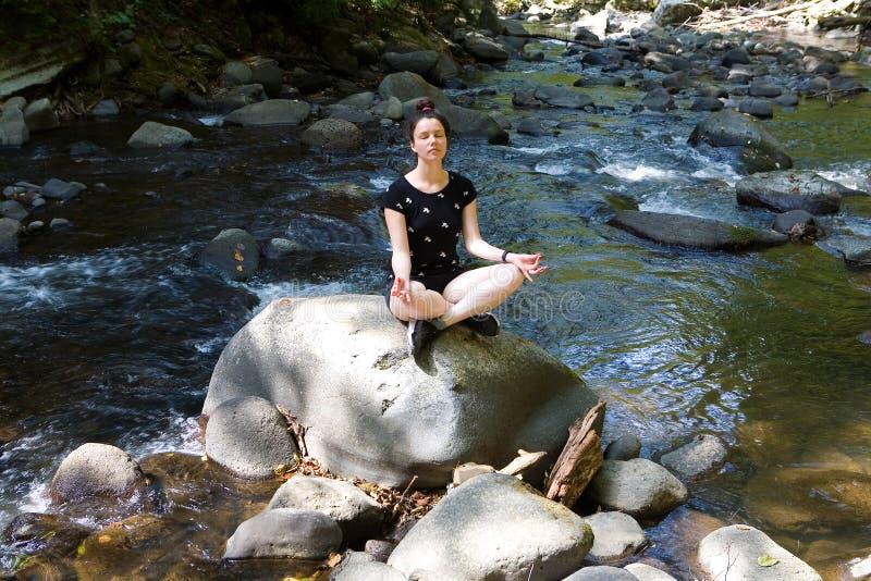 Piękna dziewczyna medytuje obsiadanie na kamieniu fotografia stock