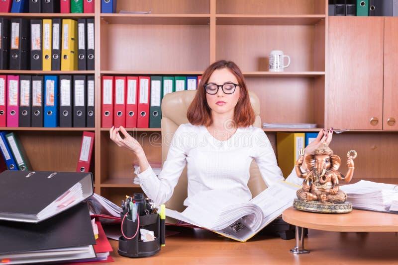 Piękna dziewczyna medytuje w biurze zdjęcie royalty free