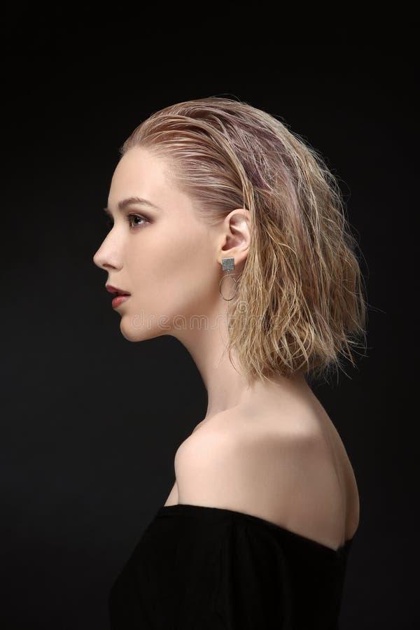 Piękna dziewczyna modela blondynka z kędzierzawym włosy na czarnym tle w profilu obrazy stock