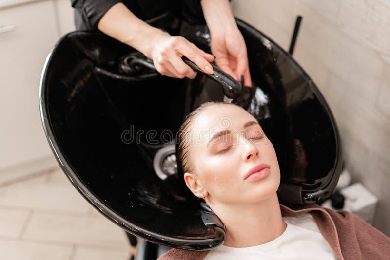 Piękna dziewczyna myje jej włosy przed ostrzyżeniem w piękno salonie włosiany domycie przy fryzjerstwem fachowy szampon zdjęcia royalty free