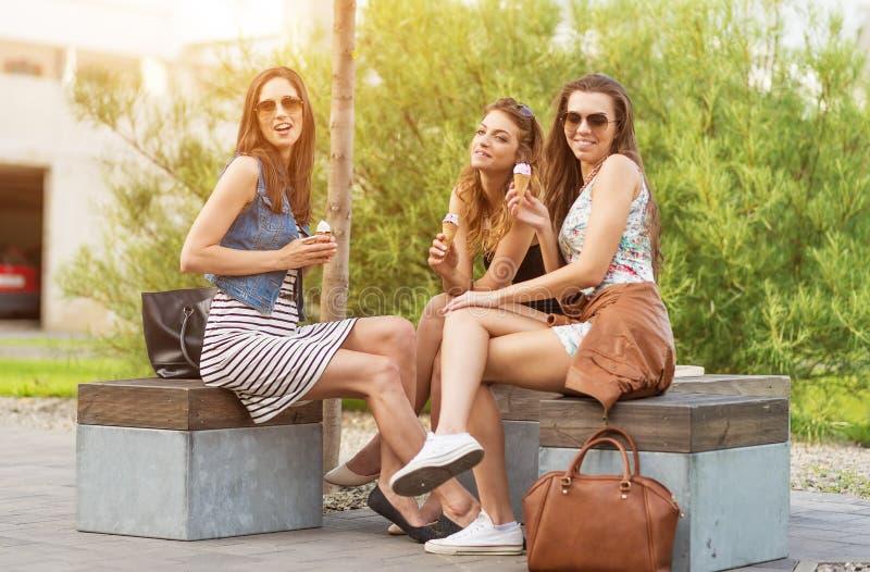 3 piękna dziewczyna na ławki łasowania lody i miasto zdjęcia royalty free