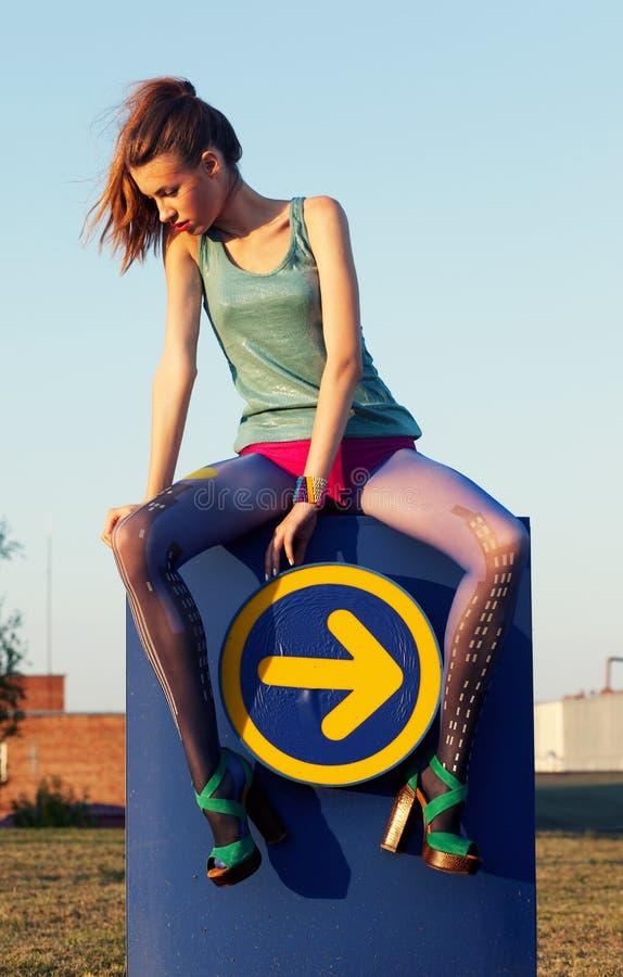 Piękna dziewczyna na drogowego znaka etykietki obsiadaniu fotografia stock
