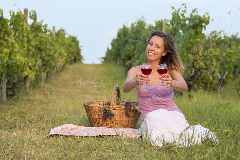 Piękna dziewczyna oferuje szkło czerwone wino w winnicy fotografia royalty free