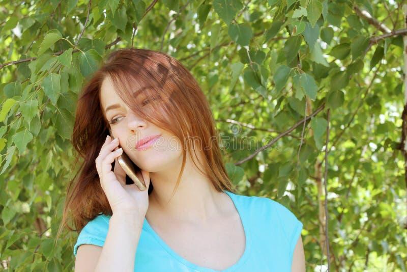 Piękna dziewczyna opowiada na telefonie przeciw tłu zieleni drzewa z ciemnym włosy obraz stock