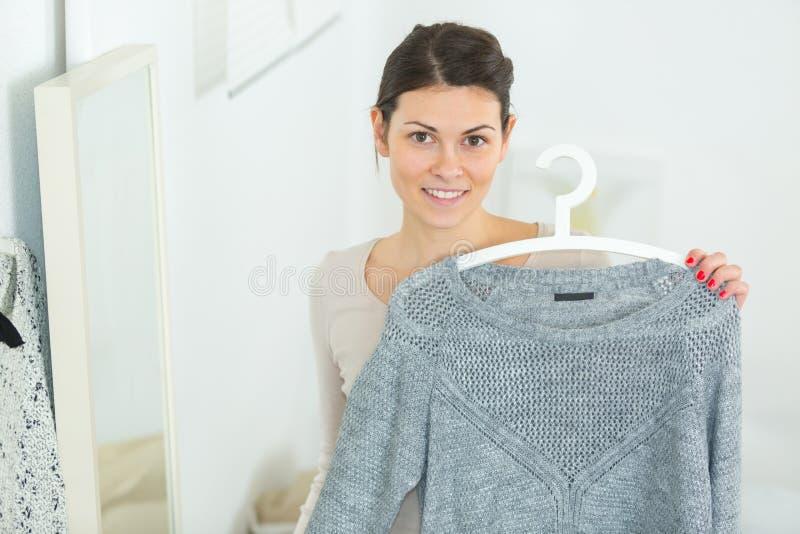 Piękna dziewczyna patrzeje kamerę podczas gdy wybierający pulower obrazy royalty free