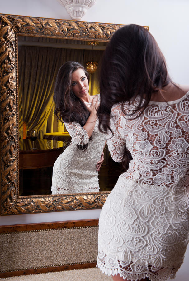 Piękna dziewczyna patrzeje w lustro w krótkiej biel sukni zdjęcie stock