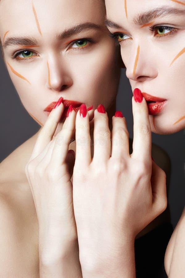 Piękna dziewczyna patrzeje w lustrze w farbie obrazy stock