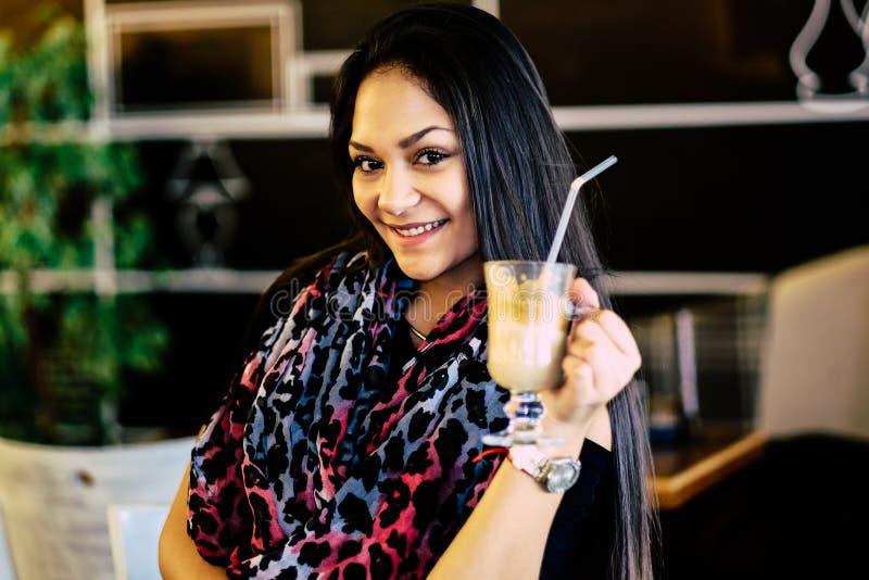 Piękna dziewczyna pije lodowego mokki potrząśnięcie w kawiarni fotografia stock