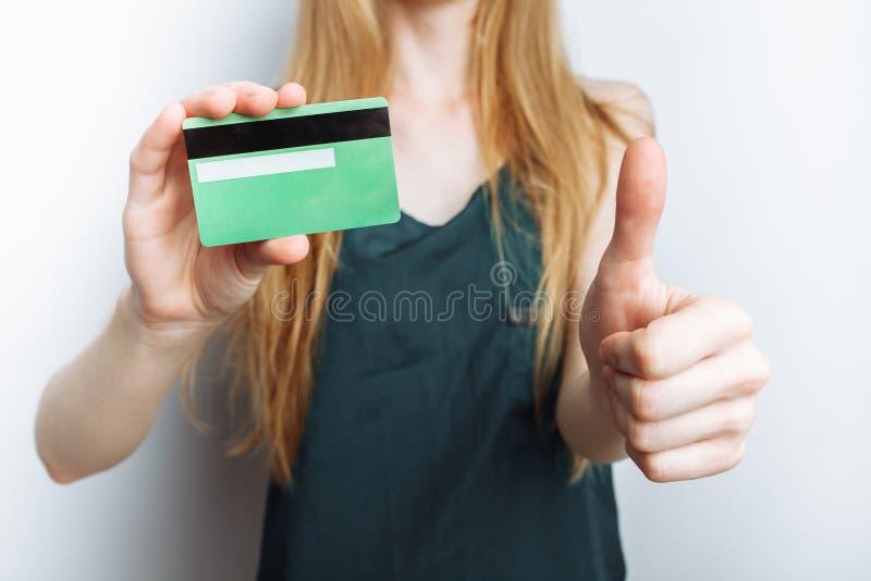 Piękna dziewczyna pokazuje bank kartę, zamazany tło, biały tło, reklamowa karta zdjęcie stock