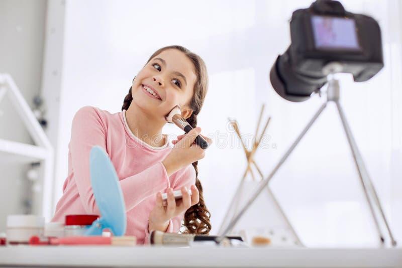 Piękna dziewczyna pozuje dla kamery podczas gdy stosować proszek zdjęcia stock