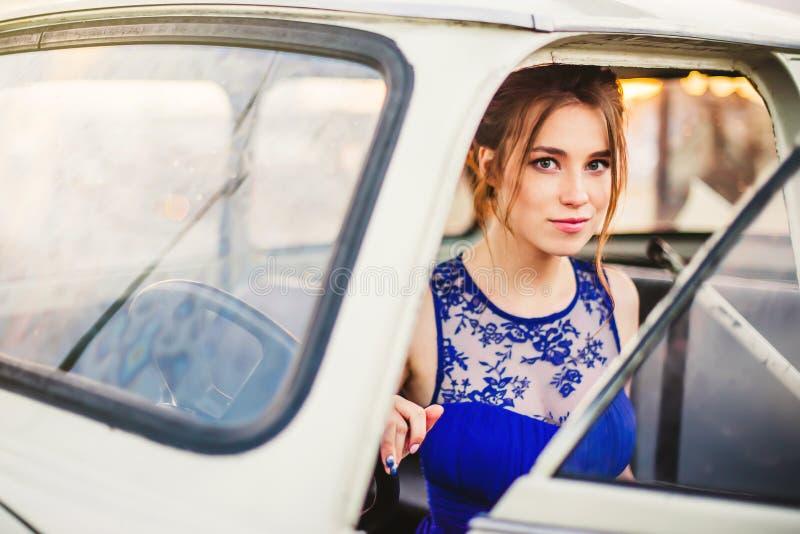 Piękna dziewczyna pozuje w białym retro samochodzie na dachu obraz royalty free
