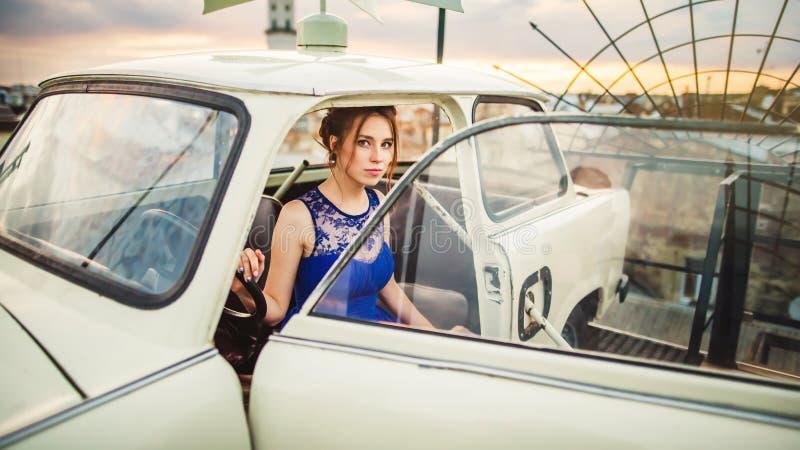 Piękna dziewczyna pozuje w białym retro samochodzie na dachu fotografia stock