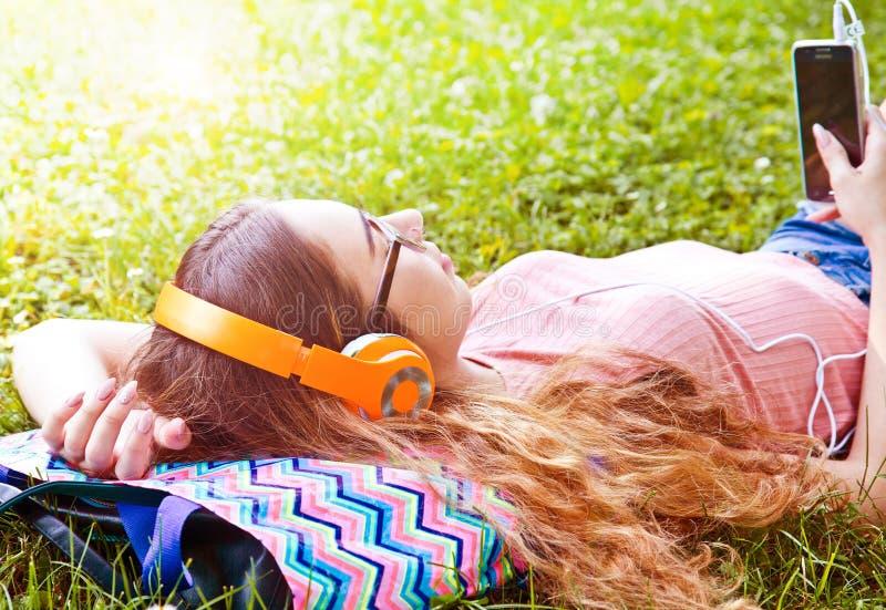 Piękna dziewczyna relaksuje i słucha muzykę w hełmofonach w th zdjęcia stock