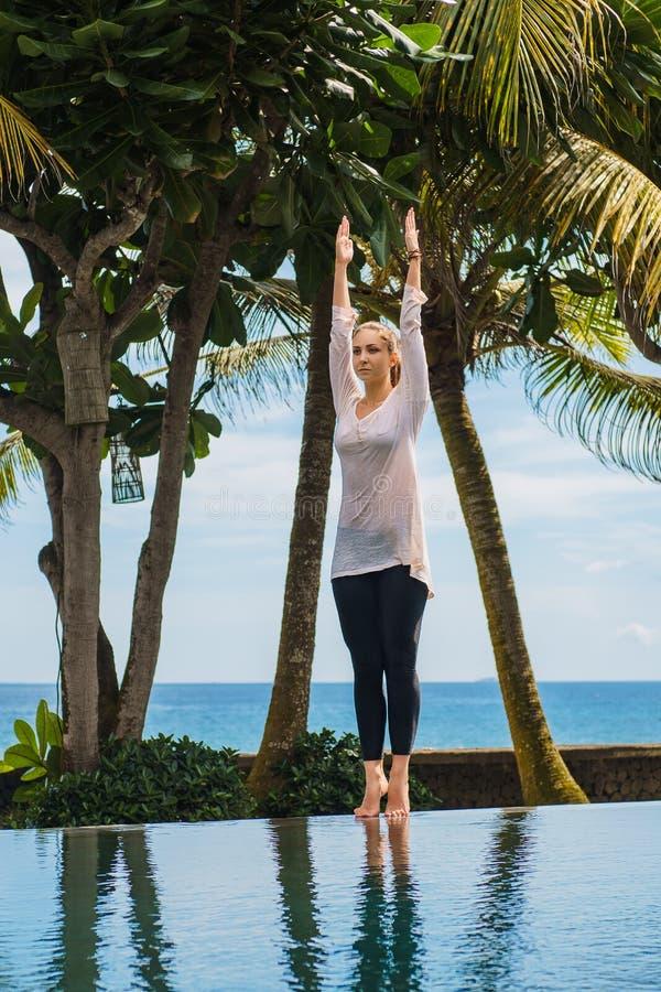 Piękna dziewczyna robi joga praktyce, medytacja rozciąga ręki w górę i stoi, na basenie obrazy royalty free
