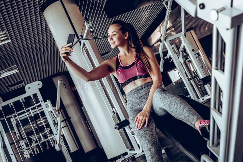 Piękna dziewczyna robi joga robi selfie na smartphone w gym obrazy royalty free