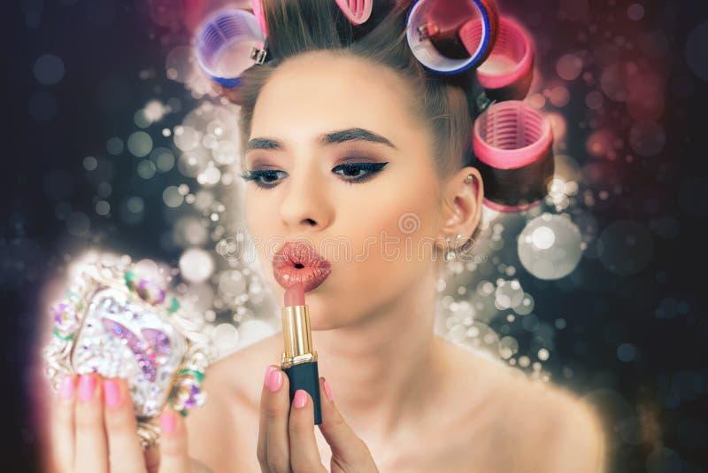 Piękna dziewczyna robi makijażowi, używać pomadkę, robi fryzurze Moda obraz stock