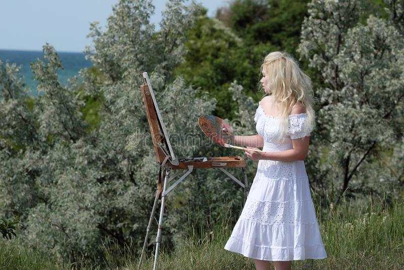 Piękna dziewczyna rysuje obrazek w parku używać paletę z farbami Sztaluga i kanwa z obrazkiem zdjęcia stock