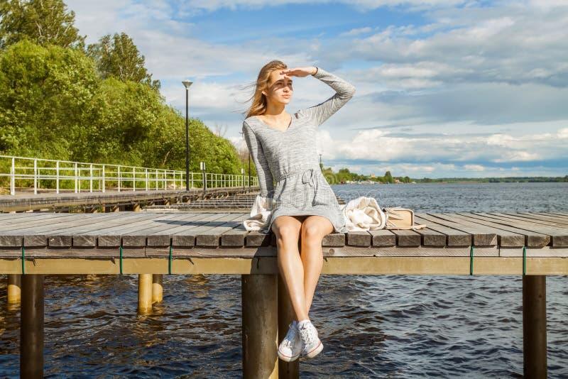 Piękna dziewczyna siedzi samotnie na rzecznym molu pod jasnym słońcem i patrzeje w odległość, chuje za jej ręką od t fotografia royalty free