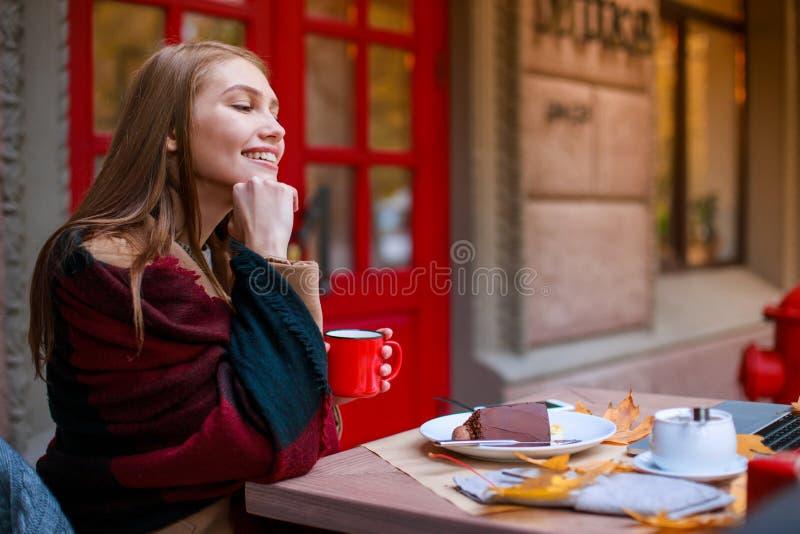 Piękna dziewczyna siedzi w kawiarni i dreamily gapi się w odległość, obrazy royalty free