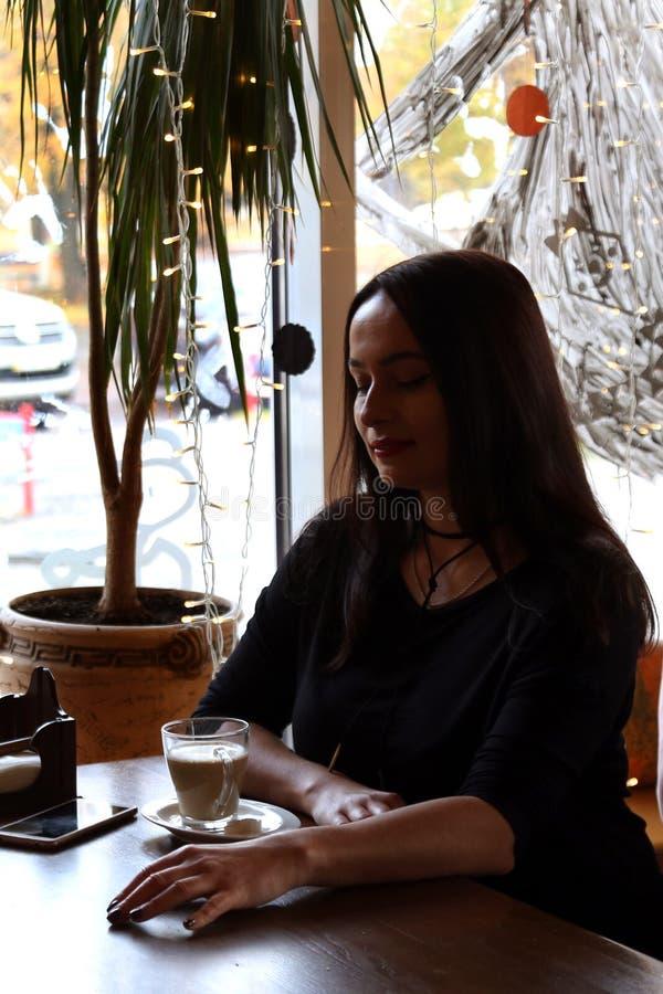 Piękna dziewczyna siedzi w kawiarni przy drewnianym stołem, cieszy się pijący kawę od szklanej filiżanki Sylwetka w backlight od obraz stock