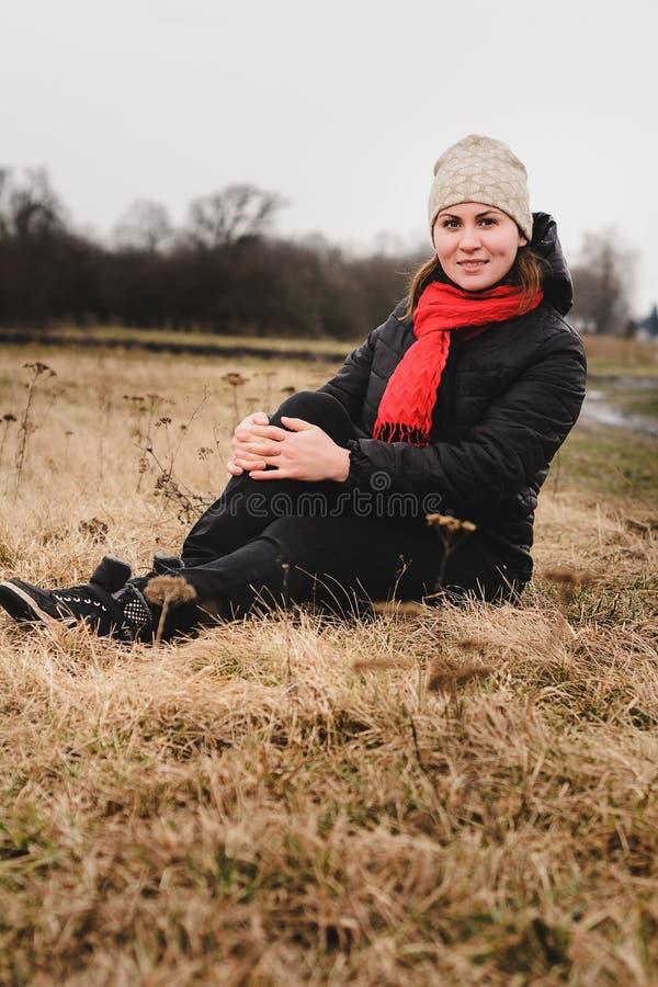 Piękna dziewczyna siedzi w polu z kapeluszem i szalikiem fotografia stock