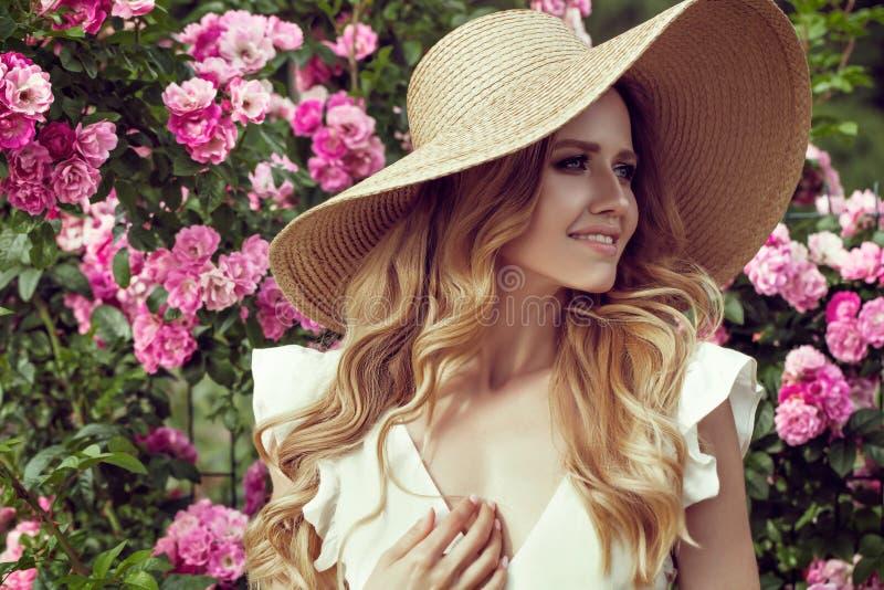 Piękna dziewczyna stoi blisko w różowym rocznika smokingowym i słomianym kapeluszu obraz royalty free